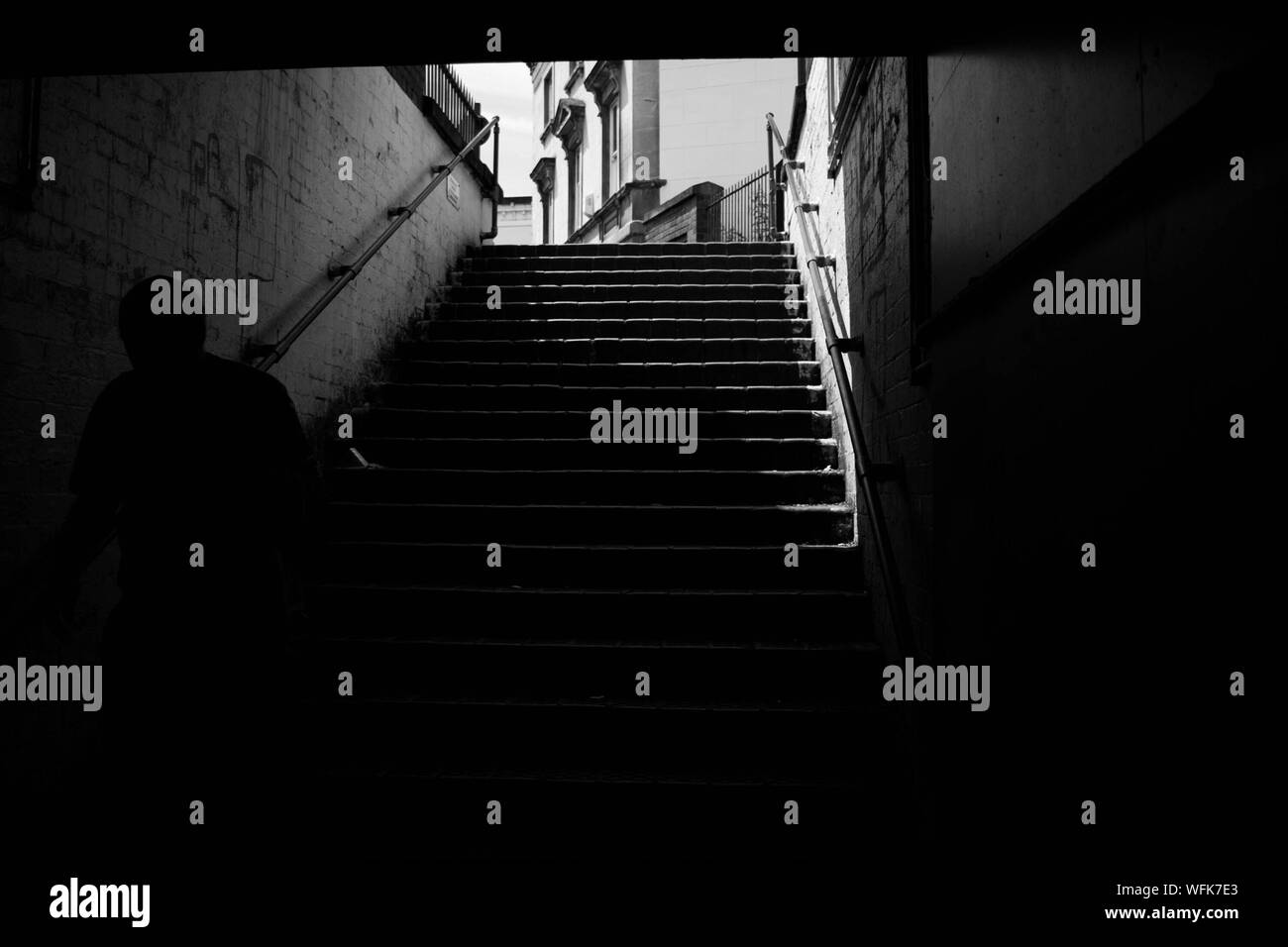 Silhouette Man Walking On Staircase In Basement Stock Photo