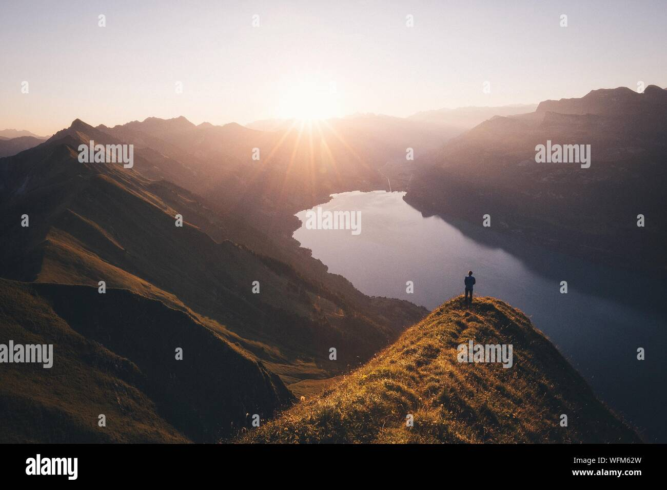 Man Standing On Cliff Looking Down On Mountain Lake Stock Photo