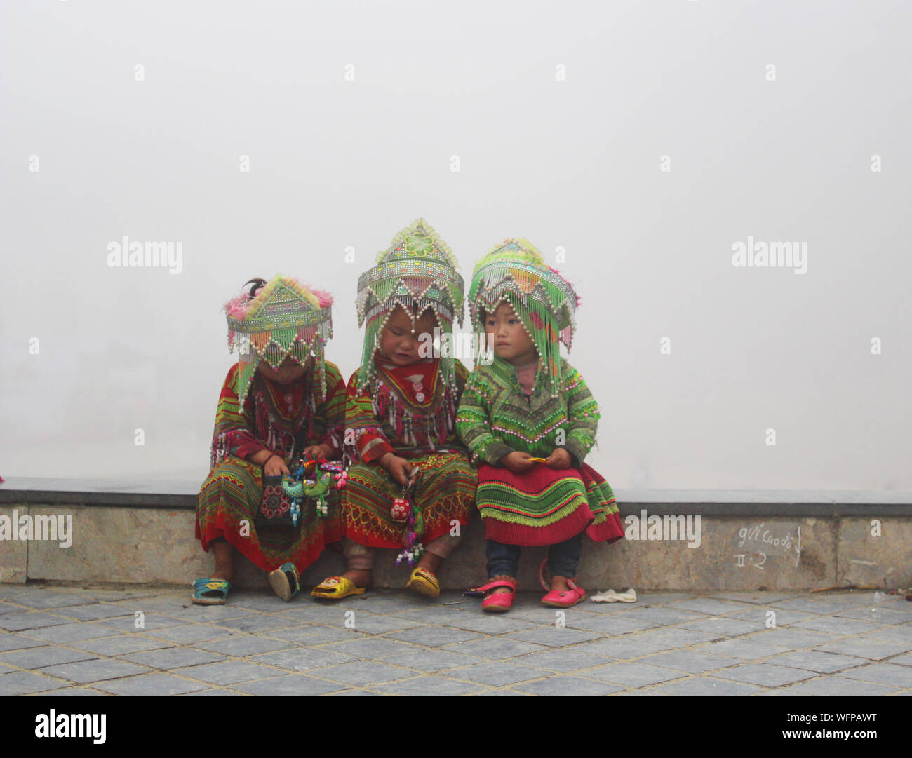 Sapa, Vietnam - june 4 2019 - small girls in traditional hmong clothes sitting on the edge on a very misty evening Stock Photo