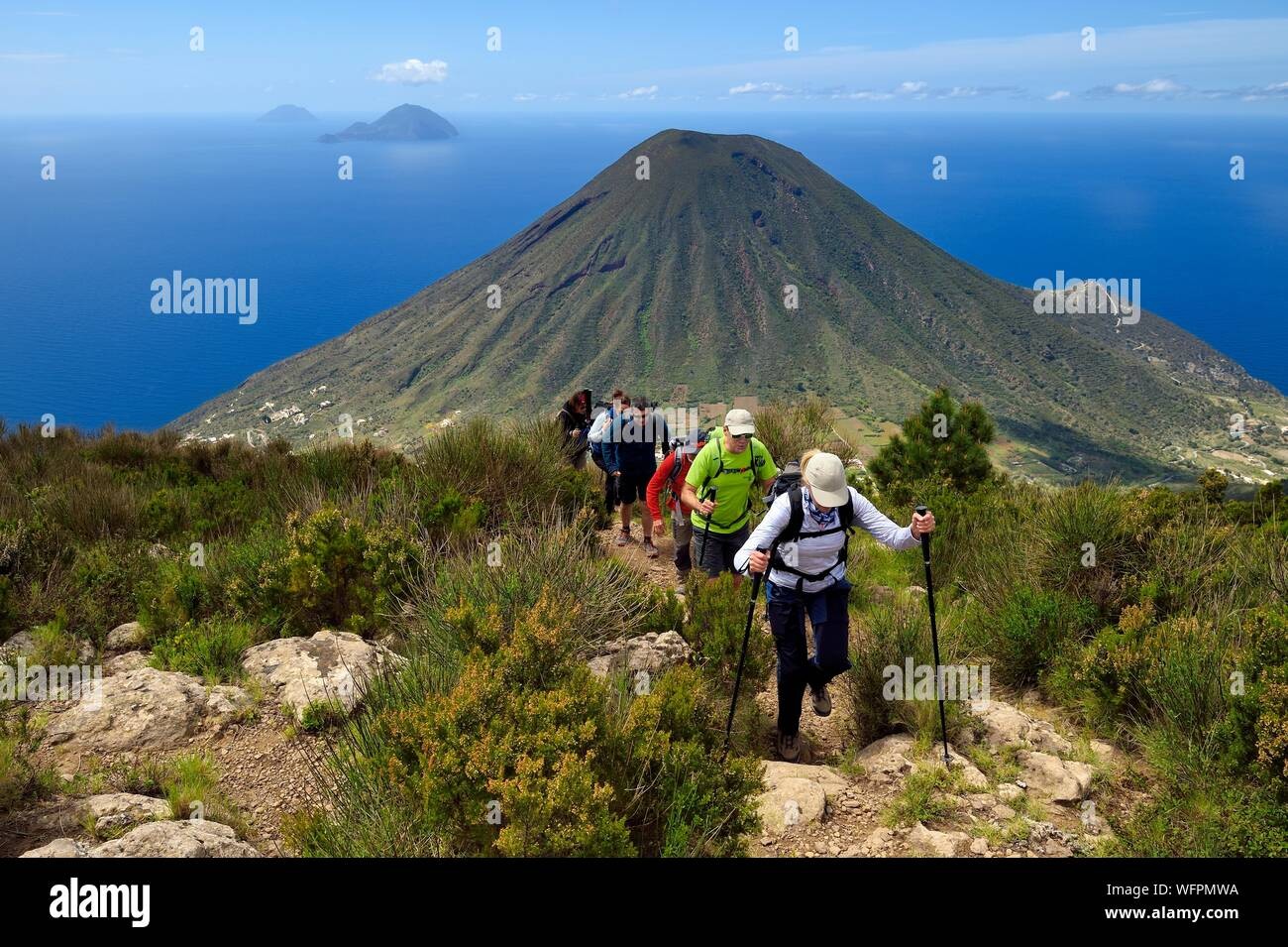 Italy, Sicily, Aeolian Islands, listed as World Heritage by UNESCO, Salina Island, hikers at the summit of the ancient volcano Monte Fossa delle Felci with the twin volcano Monte dei Porri, the islands of Filicudi and Alicudi in the background Stock Photo