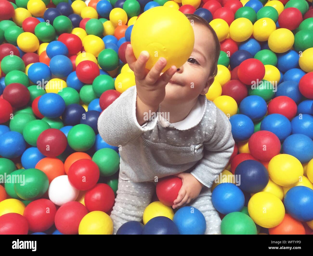 High Angle View Of Baby Boy Playing With Colorful Balls Stock Photo