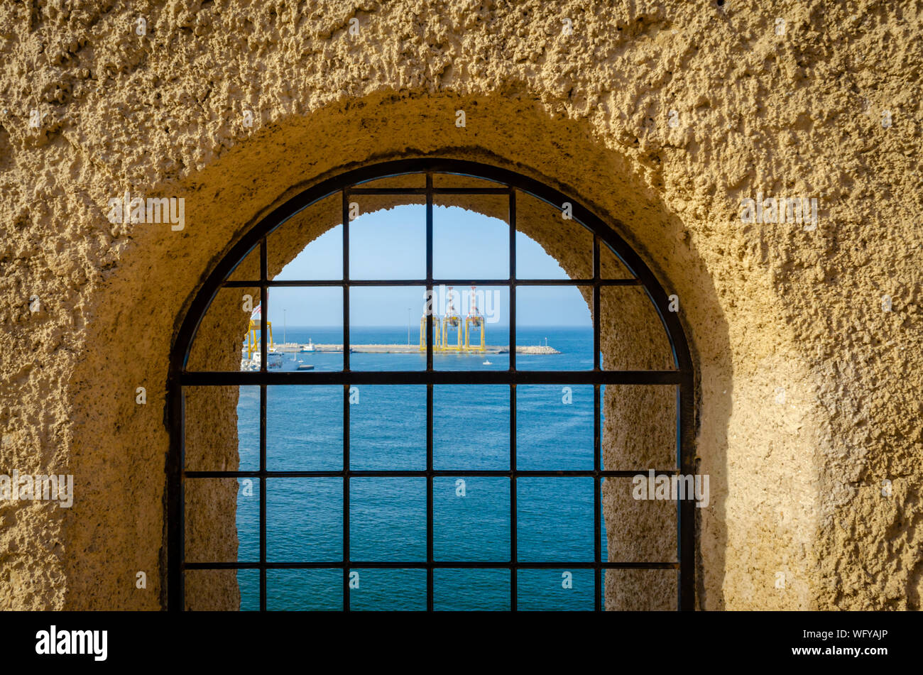 View of the sea and the port through a trap door barricaded with iron bars from the heights of the Muttrah Fort. From Muscat, Oman. Stock Photo