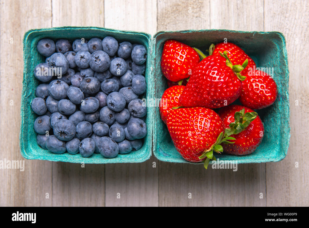 Containers of fresh ripe blueberries and strawberries from the farmers market Stock Photo