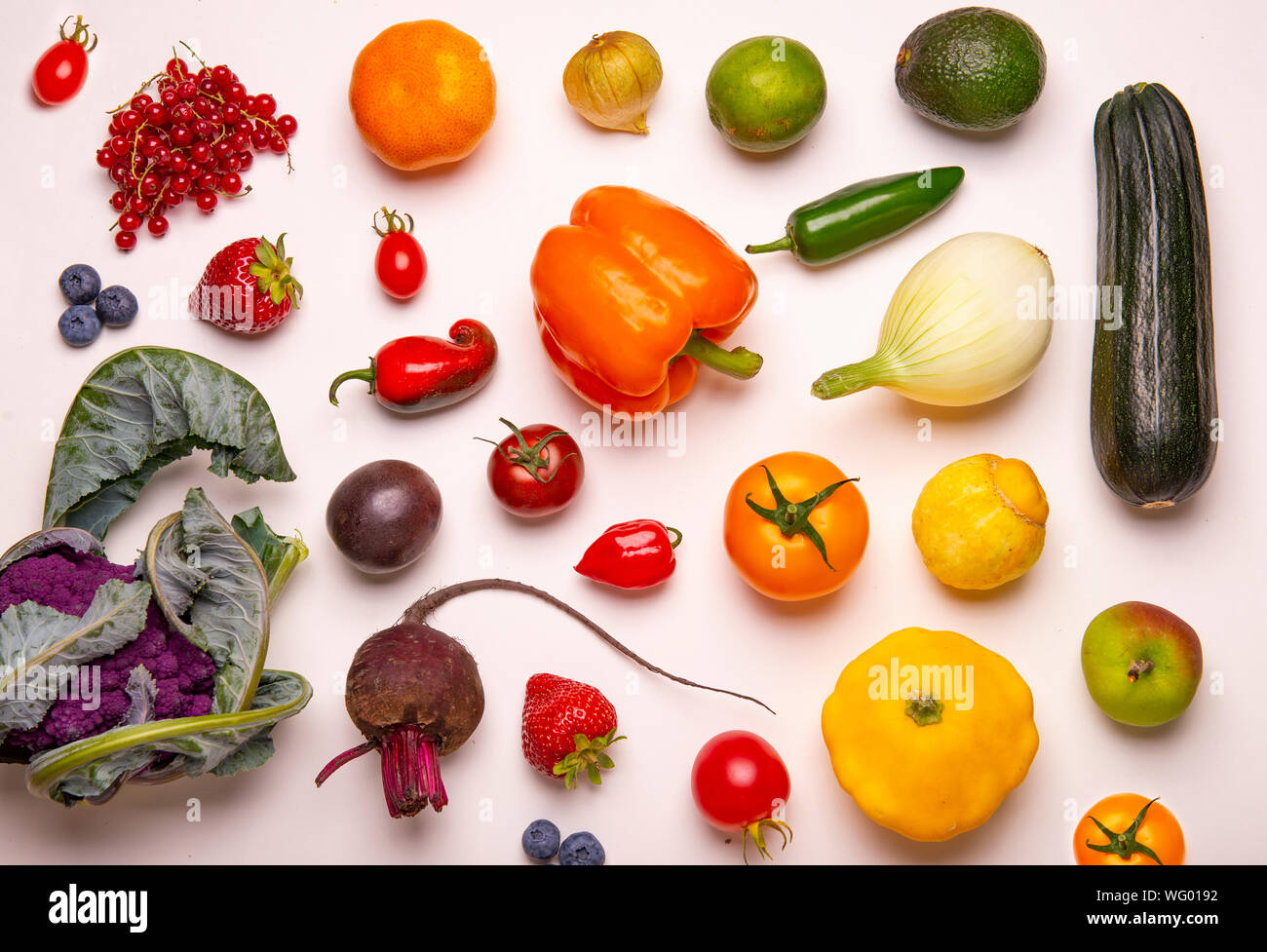 Assorted of fresh fruits and vegetables arranged in a rainbow color pattern over whiate background Stock Photo