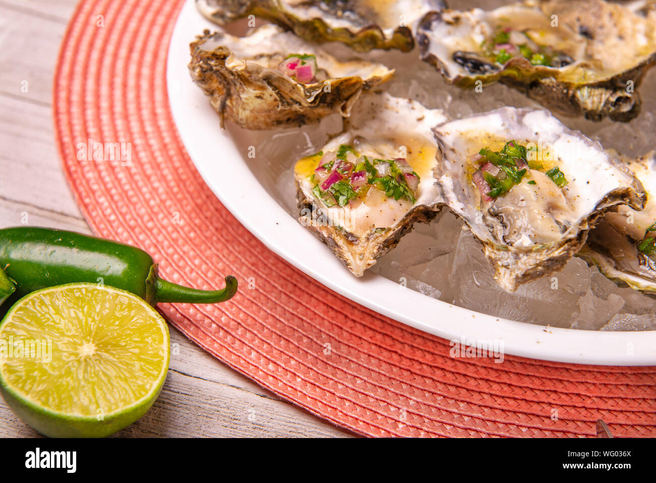 Detail of a plate with fresh shucked oysters with jalapeno & lemon mignonette over wood background Stock Photo