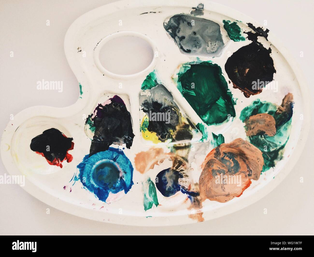 Close-up Of Multi Colored Paints In Palette On Table Stock Photo