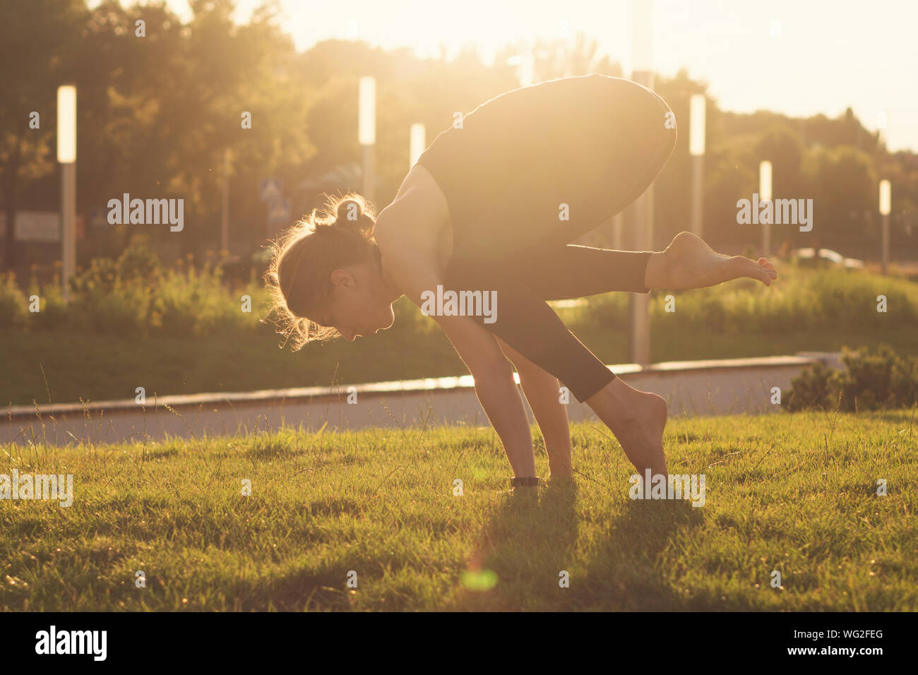 Yoga is the best holistic workout. Mental and physical health. Yoga instructor with do sport. Girl performs yoga in a park on International Yoga Day Stock Photo
