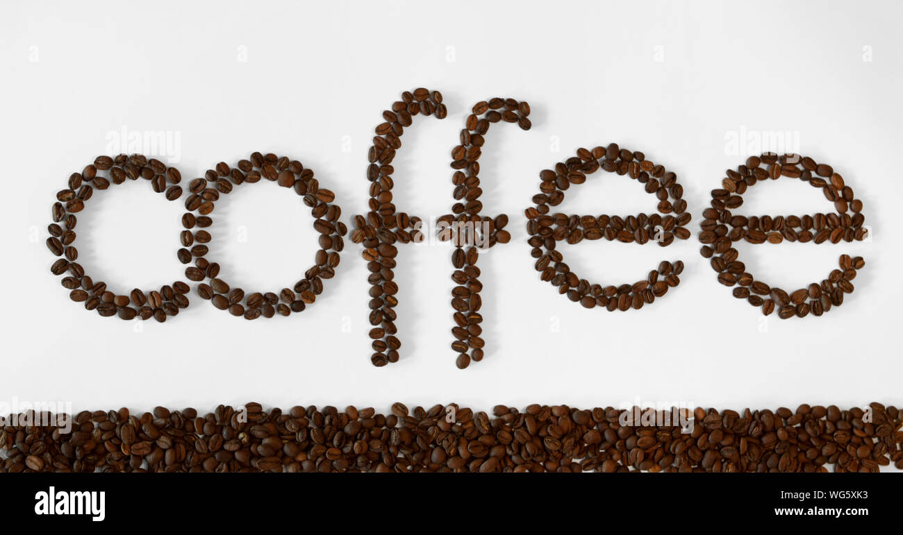 Close-up Of Coffee Text Made With Beans Over White Background Stock Photo