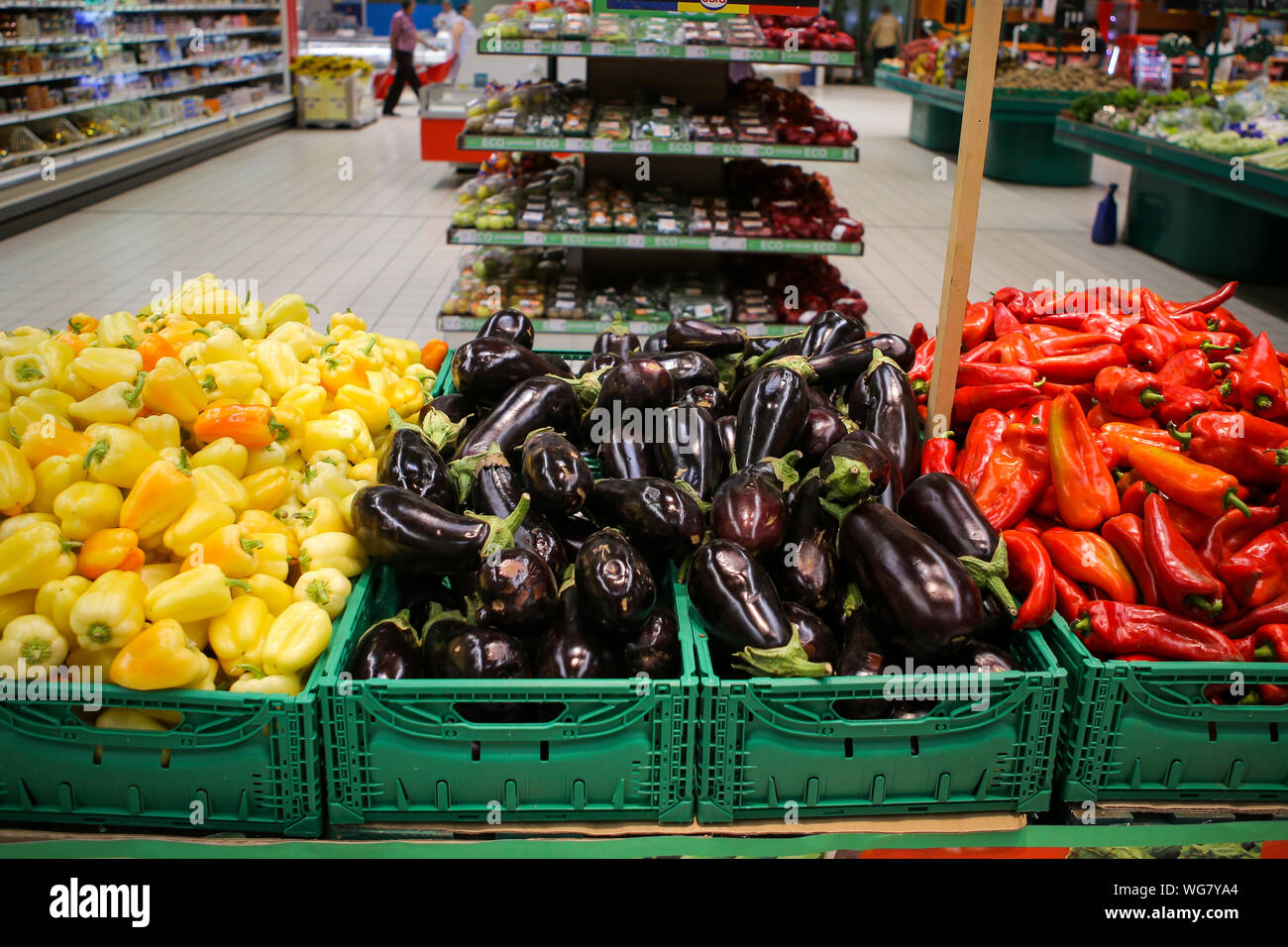 Red sweet peppers, eggplants and yellow sweet peppers on the fruits and vegetables aisle in a store Stock Photo