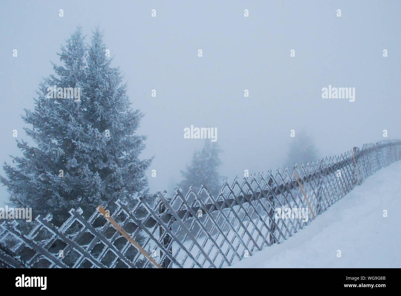 Fence By Snow Covered Field Against Sky Stock Photo