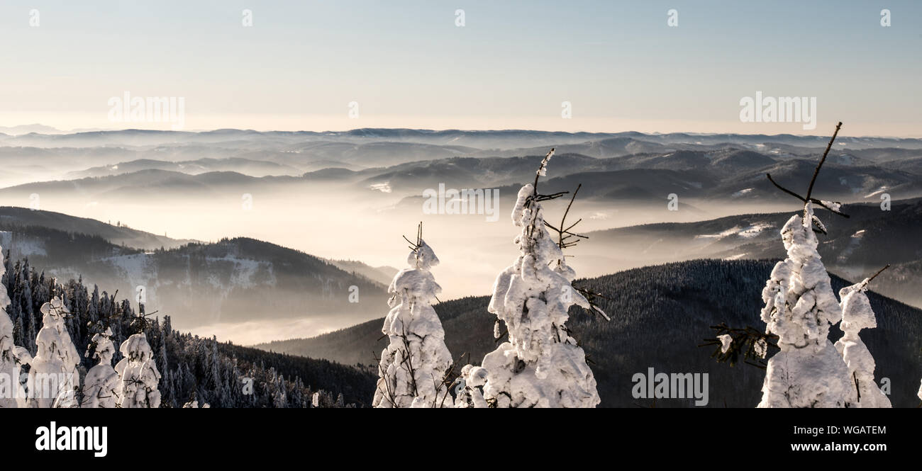 mountain panorama with many mountain ranges, mist and clear sky above from hiking trail bellow Lysa hora hill in Moravskoslezske Beskydy mountains in Stock Photo