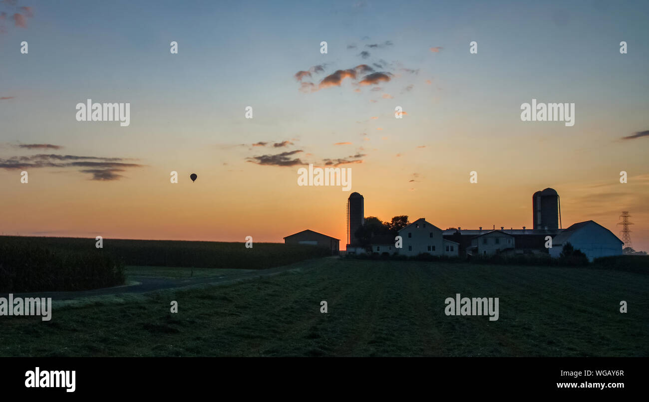 Sunrise Over an Amish Farm with Blues and Reds With a Hot Air Balloon Floating By on a Clear Summer Morning Stock Photo