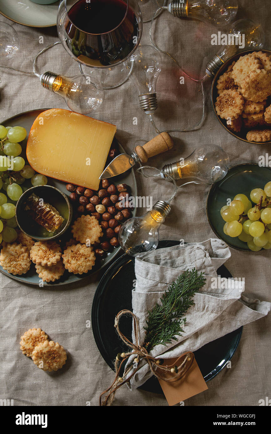 Home Christmas Or New Year Dinner Table Set With Wine Cheese Plate Appetizers Lightning Garland Xmas Decoration And Empty Plate With Cloth Napkin Stock Photo Alamy