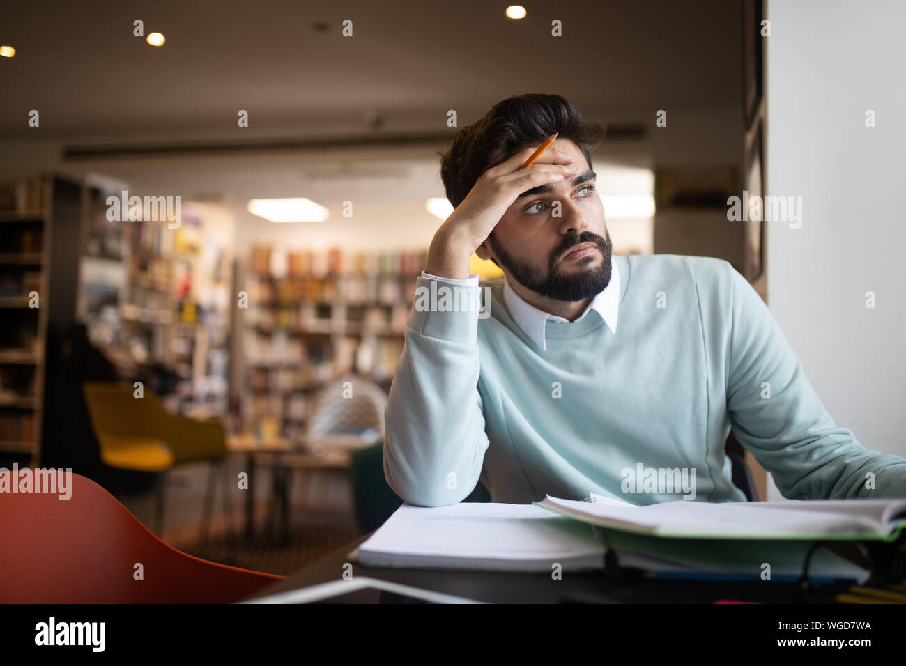 People, education, studying, exams and school concept - tired student learning in library Stock Photo