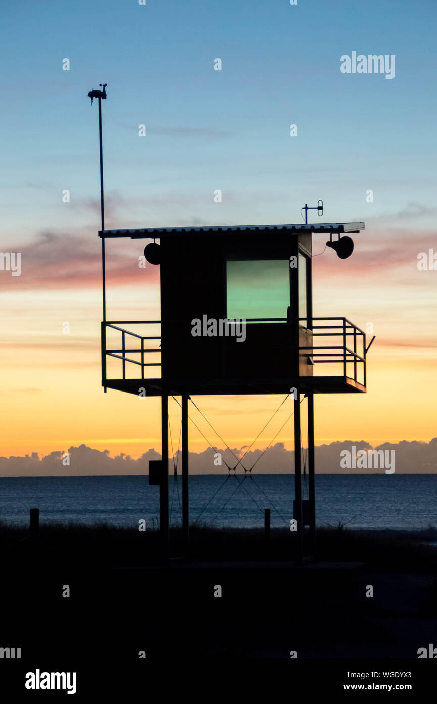 Scenic View Of Silhouette Lookout Tower On Beach Against Cloudy Sky Stock Photo