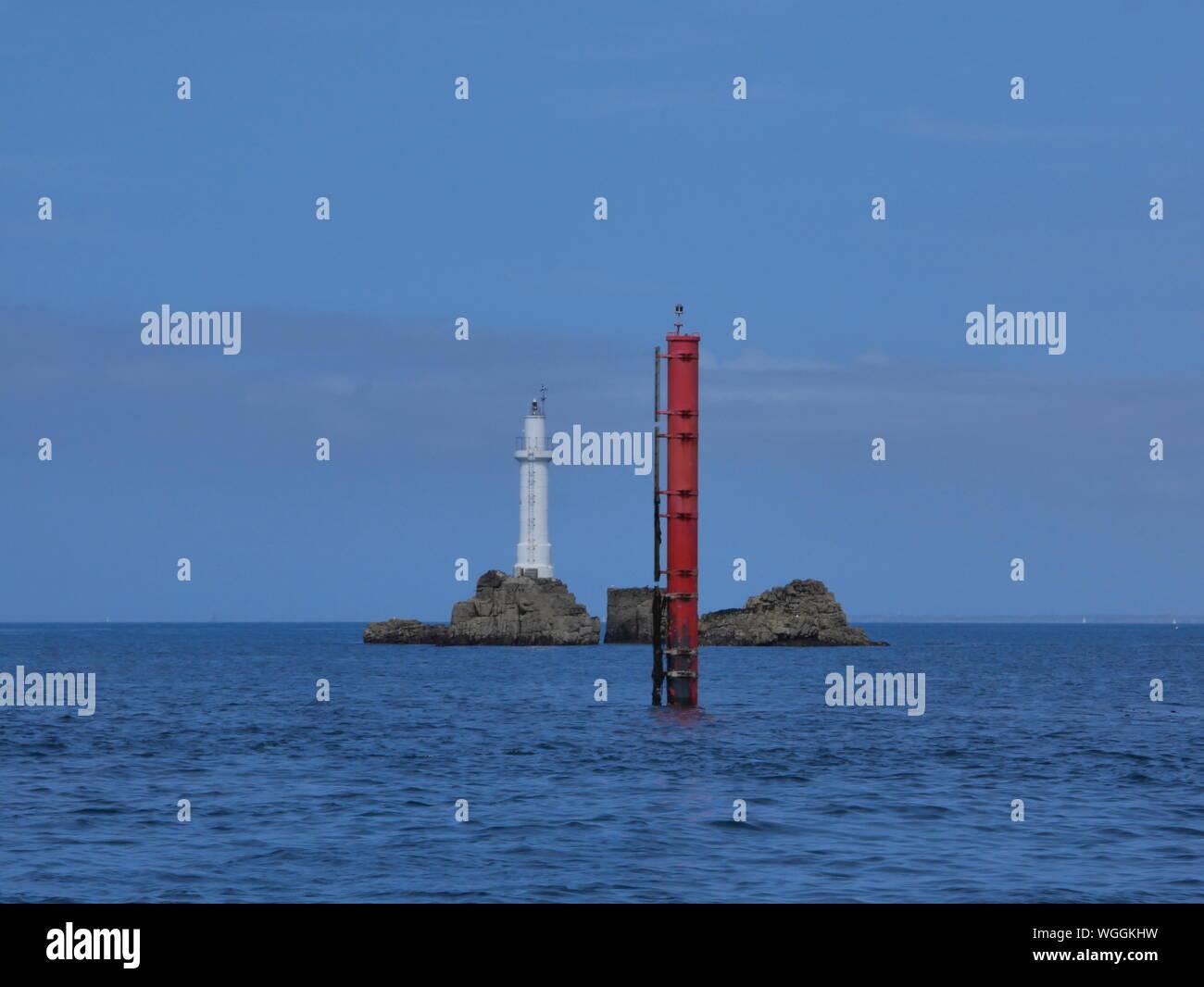 phare des trois pierres , phare blanc de l'île de molène , phare sur rocher en pleine mer , balise rouge , archipel de molène , île de ouessant       . Stock Photo