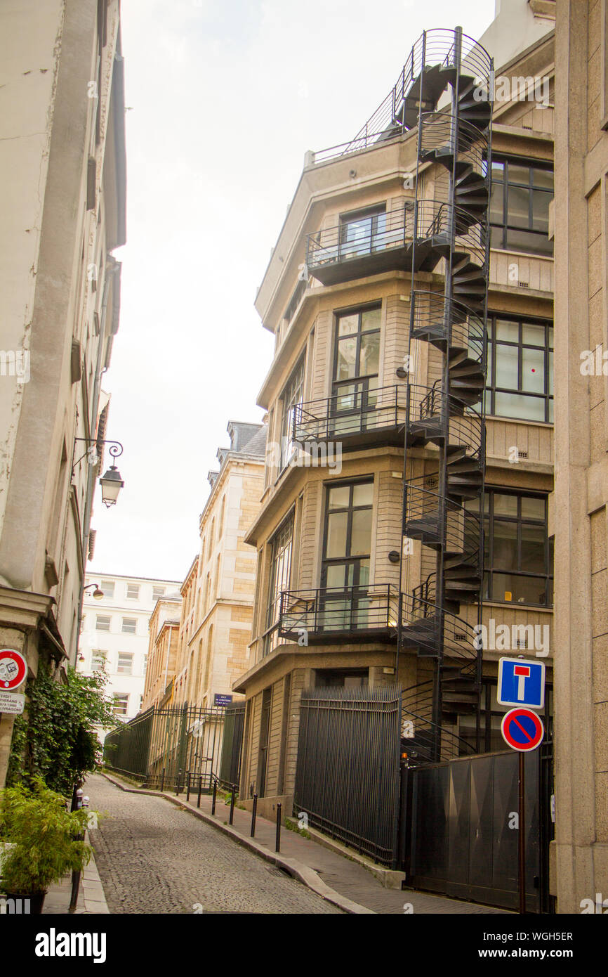 Paris, France - July 7, 2018: Narrow street of Paris and a building with a spiral staircase Stock Photo