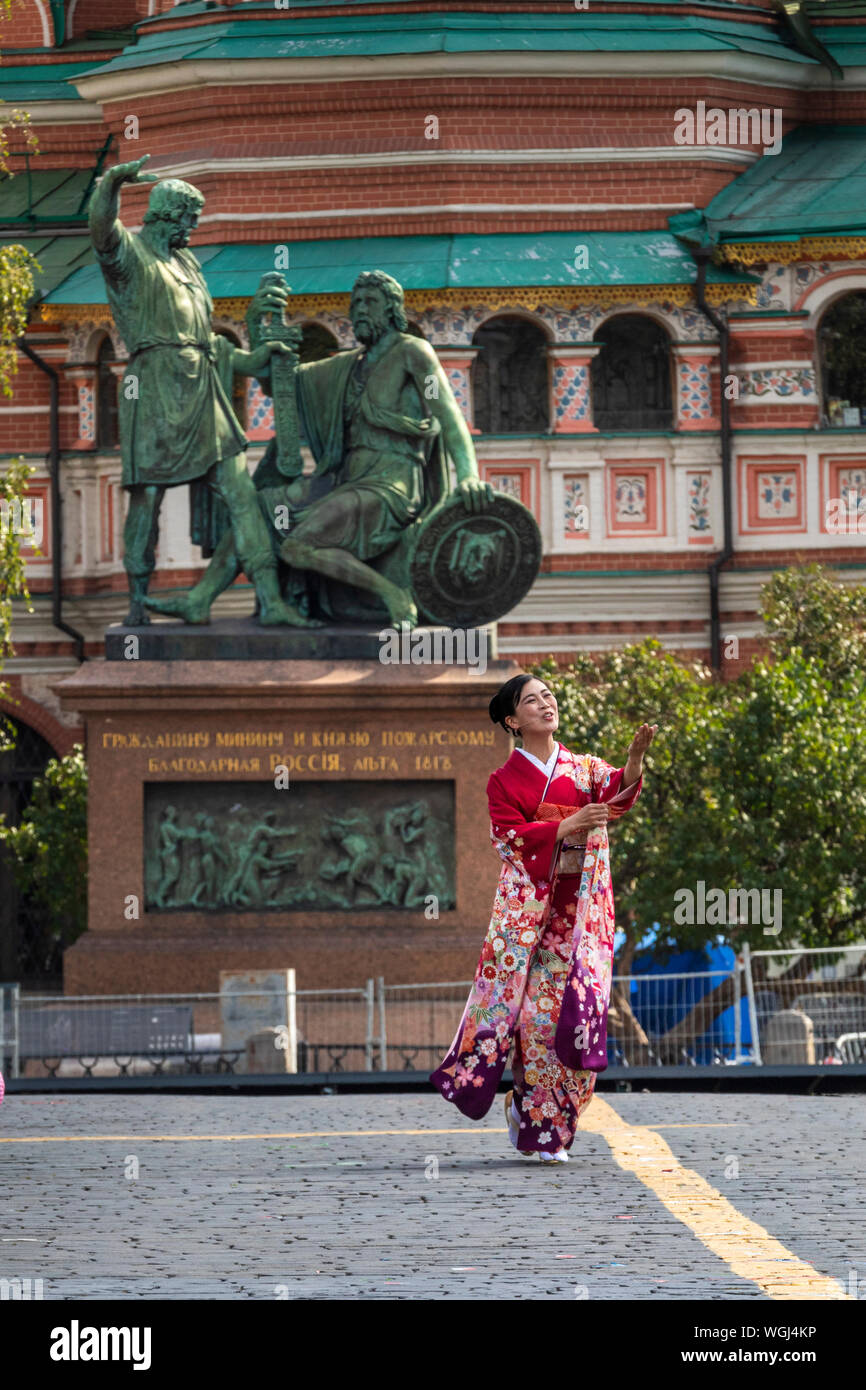 A woman in traditional japanese clothes walks on Red Square during performance of The Japan Ground Self-Defense Force (JGSDF) Central Band in Moscow Stock Photo