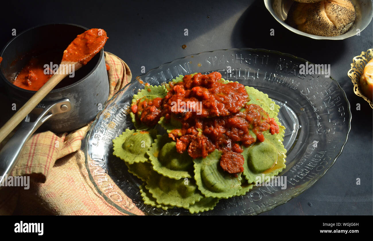 High Angle View Of Spinach Ravioli With Red Marinara Sauce In Plate On Table Stock Photo