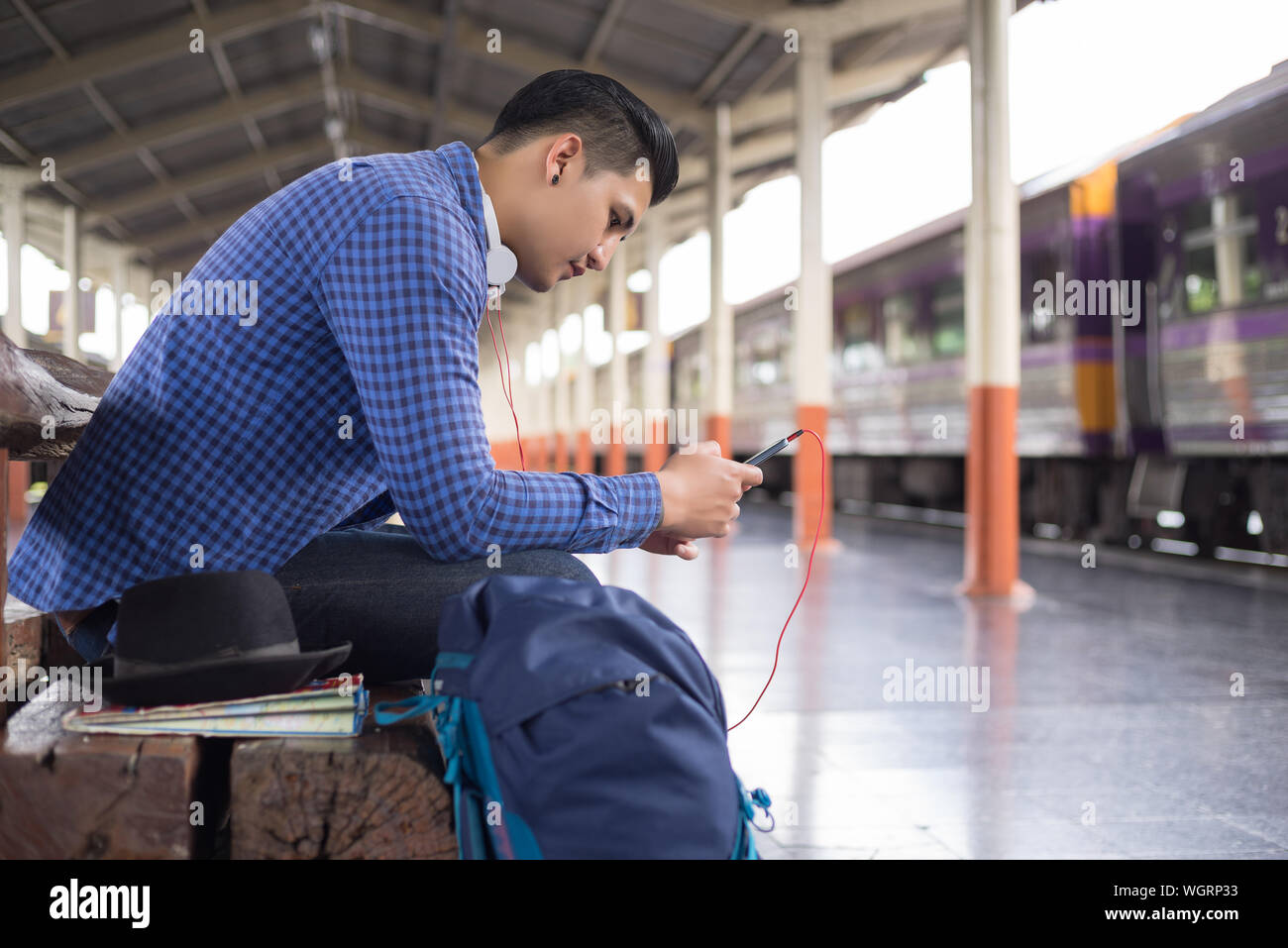 Side View Of Man Using Mobile Phone While Sitting At Railroad Station Platform Stock Photo