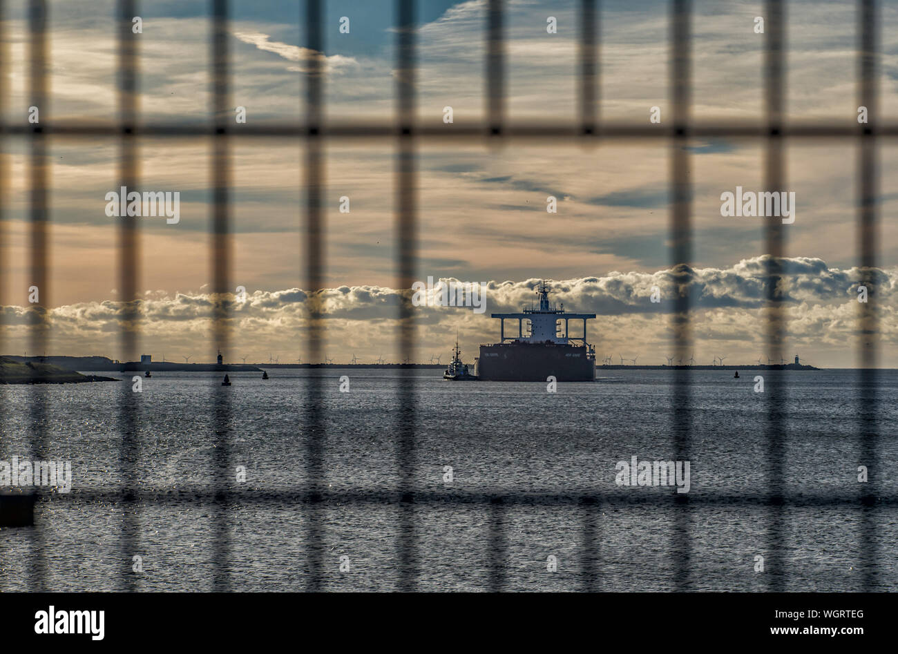 Boat Moving In Sea Seen Through Fence Against Cloudy Sky During Sunset Stock Photo