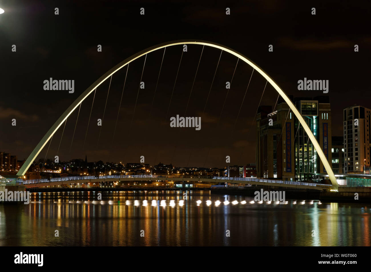 Illuminated Gateshead Millennium Bridge Over River At Night Stock Photo