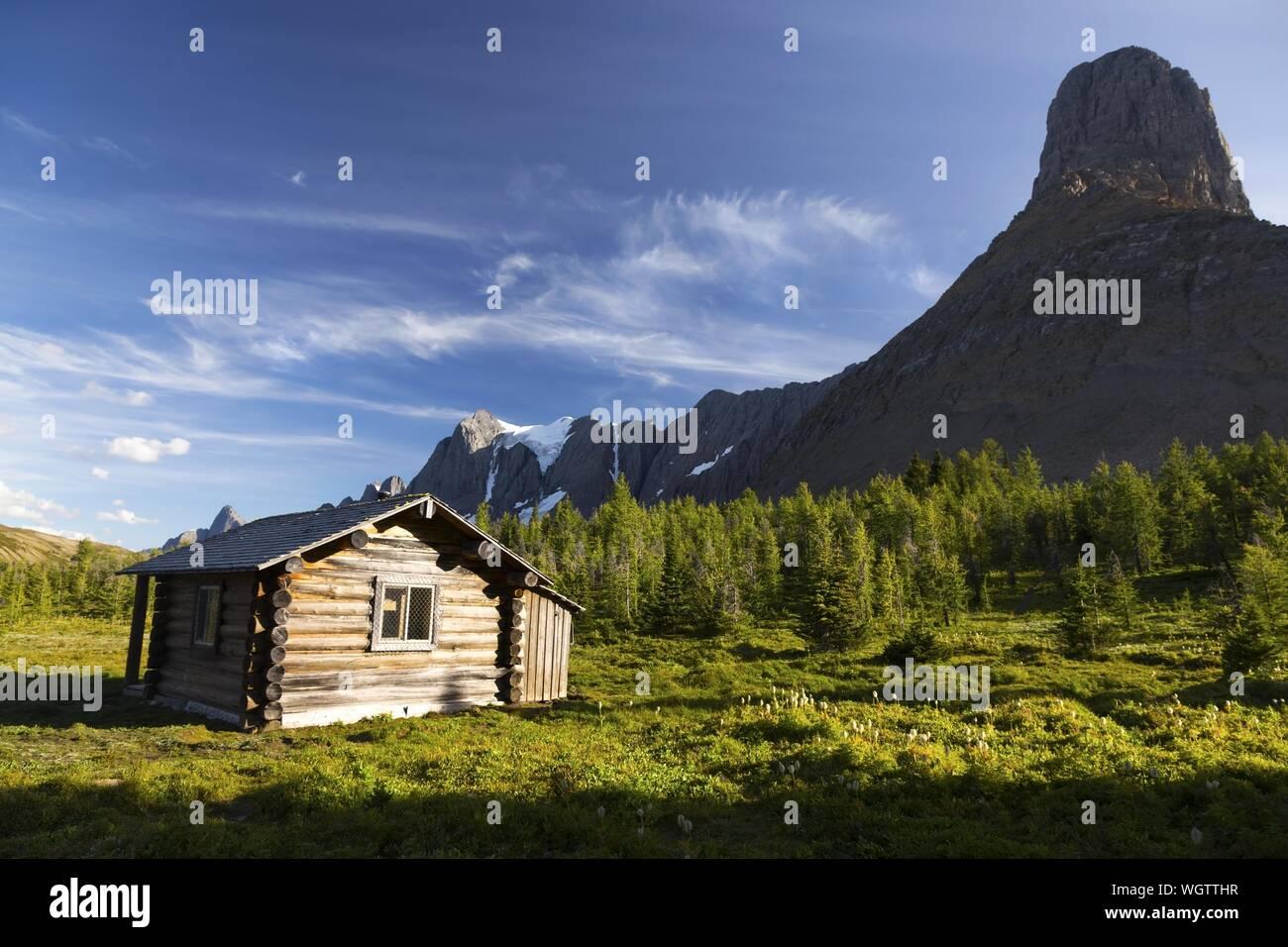 Heritage Landmark Outfitter Log Cabin on Green Alpine Meadow near Wolverine Pass below Rockwall Mountain Peak, Kootenay National Park Canadian Rockies Stock Photo