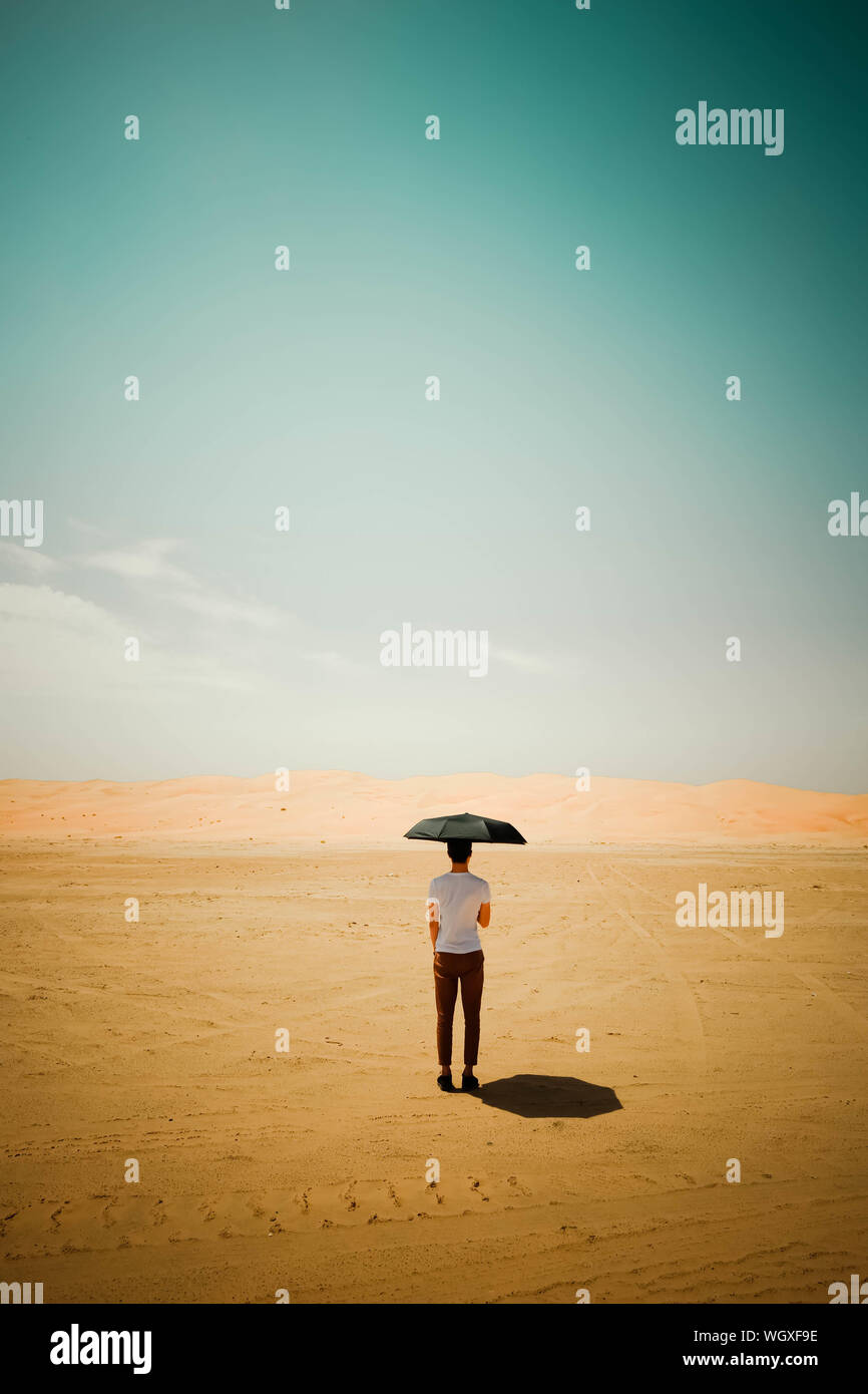 Rear View Of Man Standing In Desert With Umbrella Stock Photo