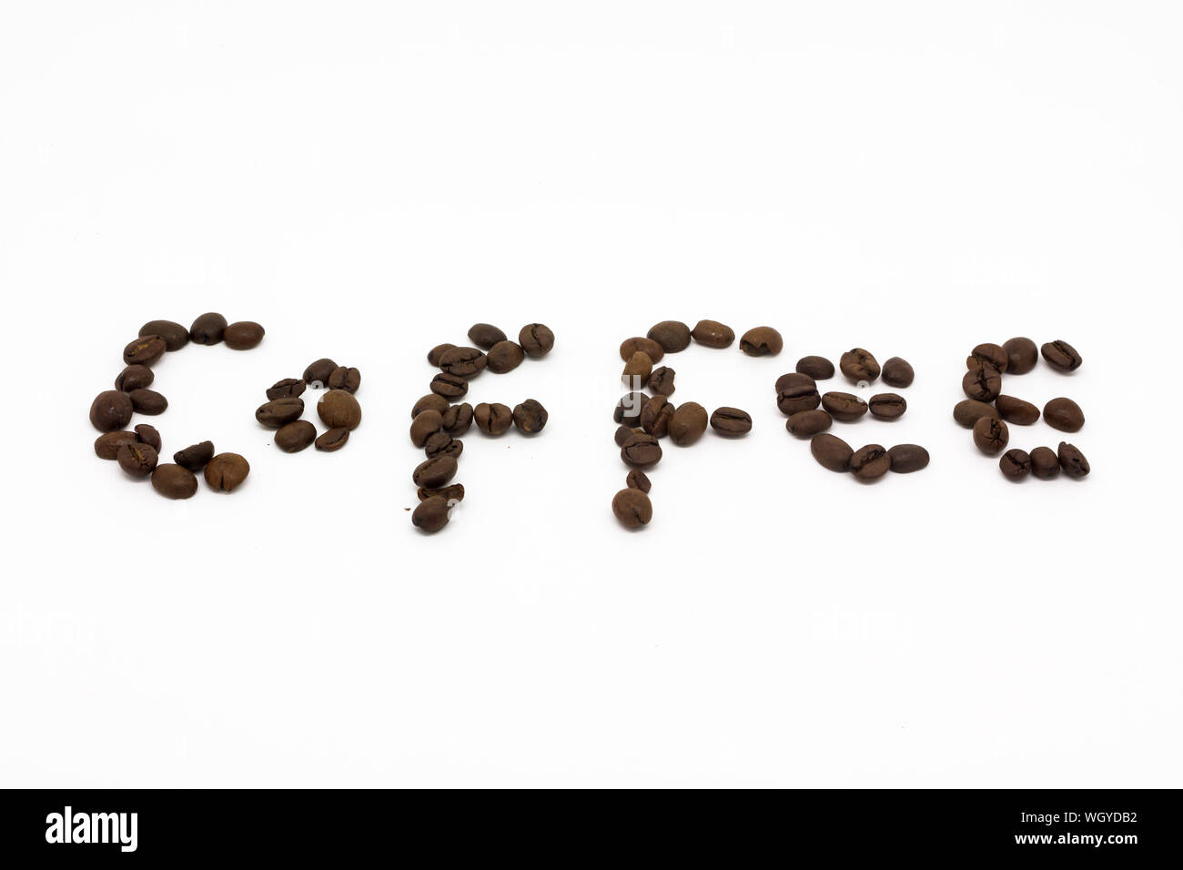 Text Made By Roasted Coffee Beans Over White Background Stock Photo