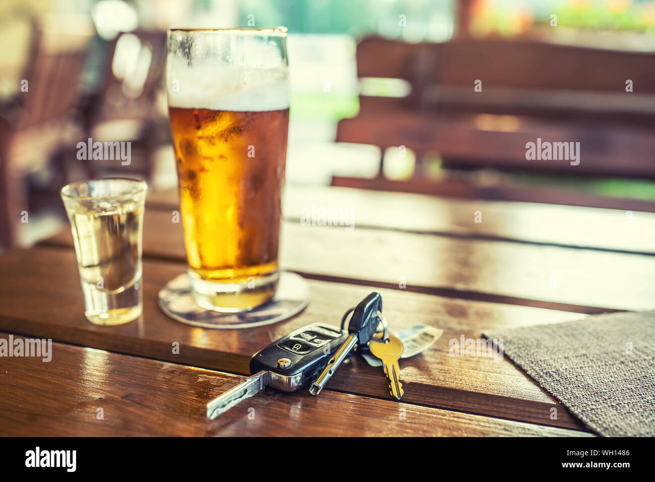 Car keys and glass of beer or distillate alcohol on table in pub or restaurant Stock Photo