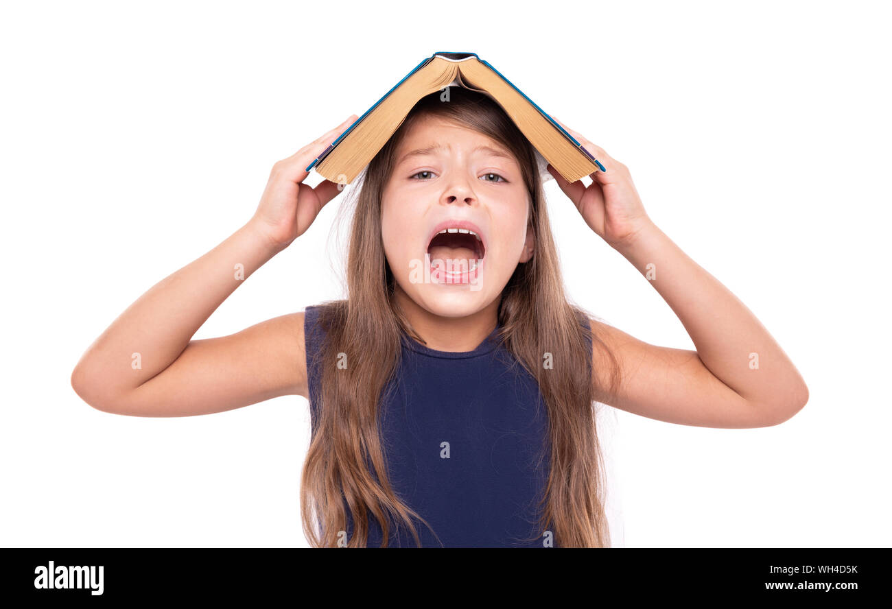 Little girl with an open book on her head is angry. Stock Photo