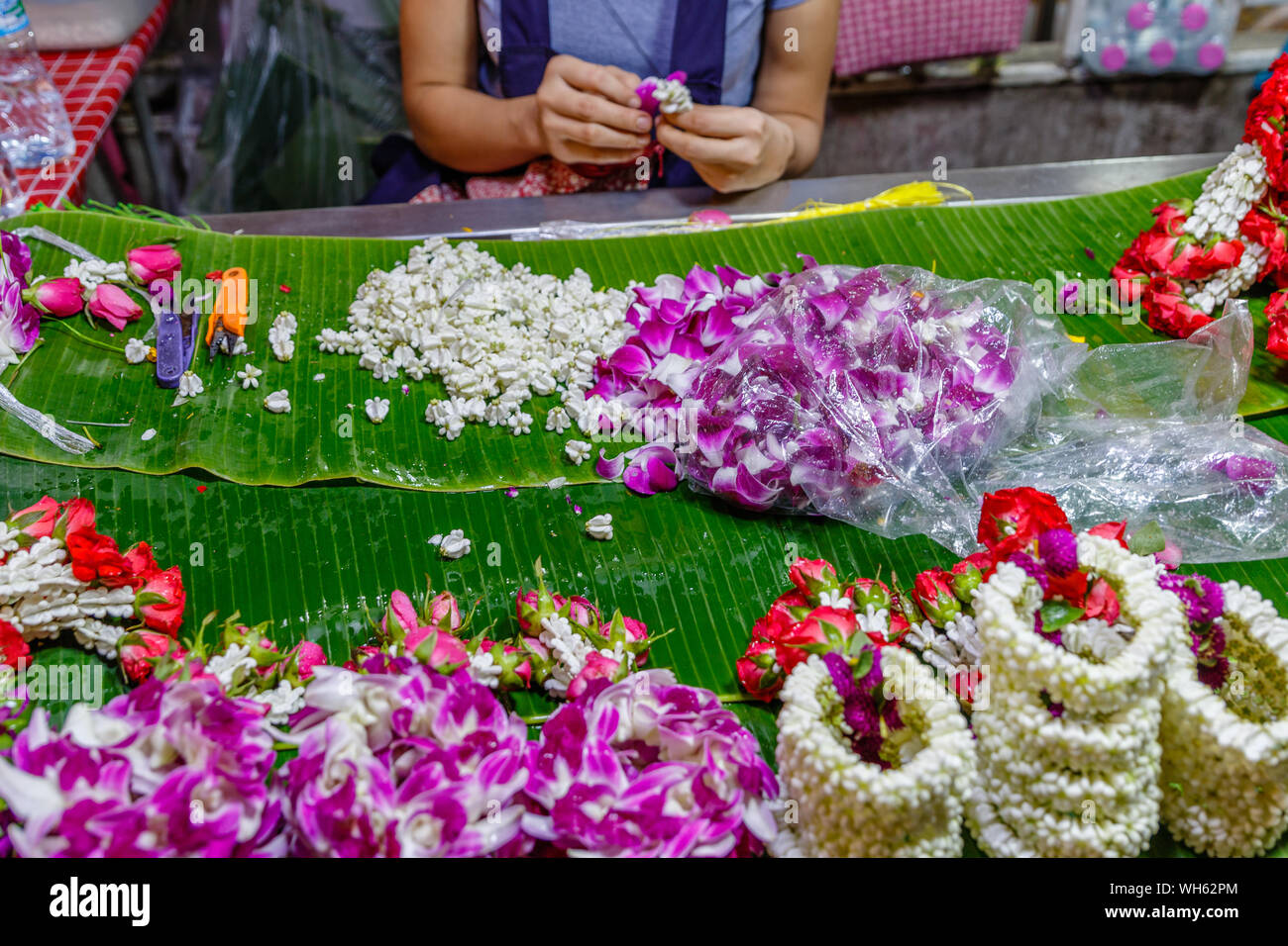 Woman making Phuang malai, traditional Thai flower garland offerings with jasmine and orchids at Pak Khlong Talat, Bangkok flower market. Thailand. Stock Photo