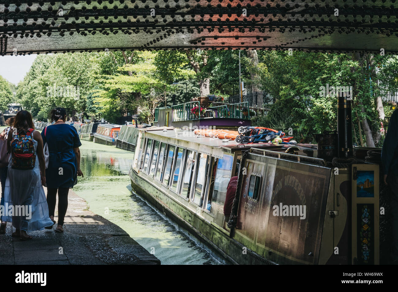 London, UK - July 18, 2019: People and tour boat passing under the bridge on Regents Canal in Little Venice, London, a tranquil area of the city where Stock Photo