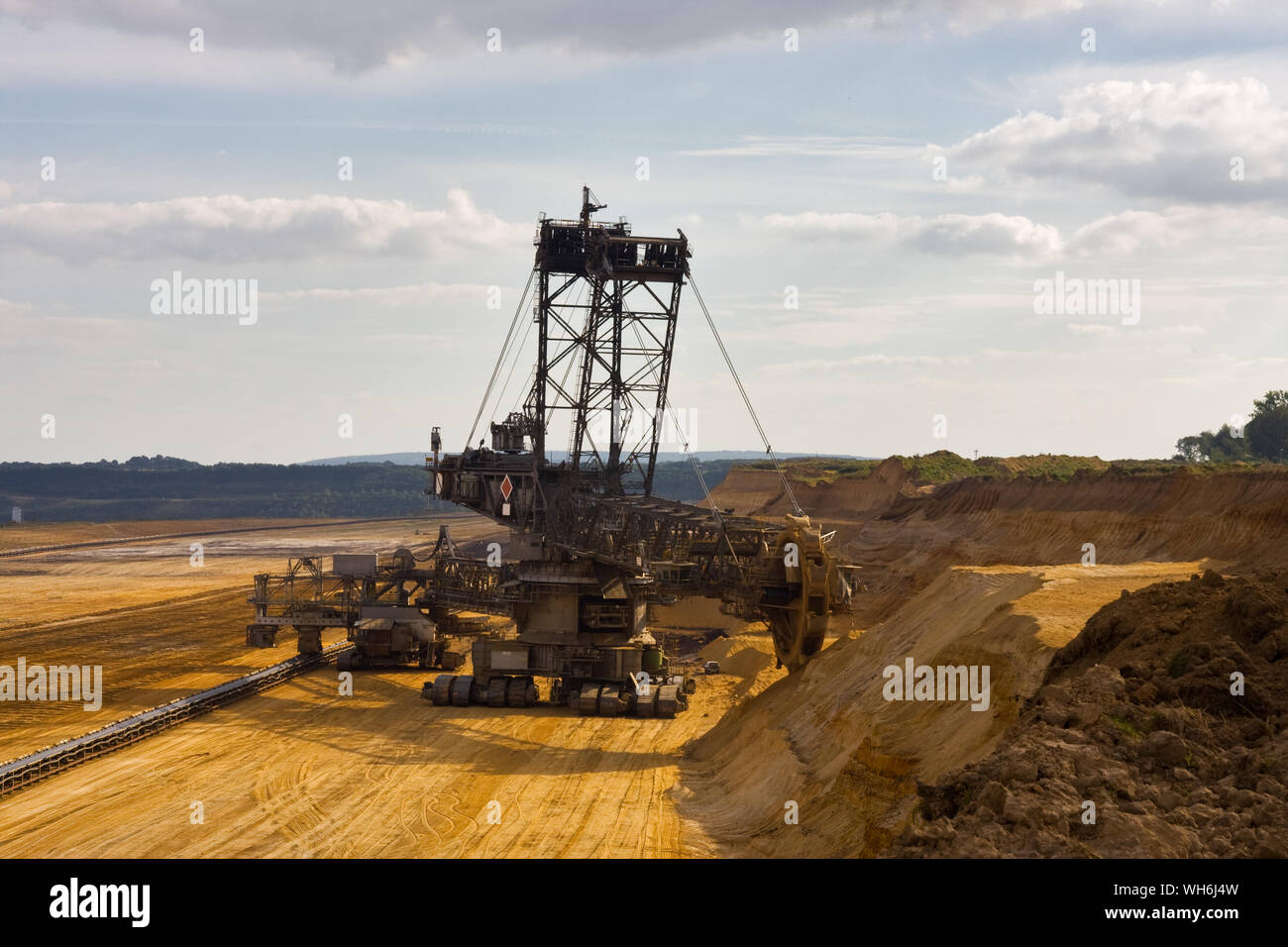 Giant bucket wheel excavator taking away the layers of ground before digging the brown coal. Stock Photo
