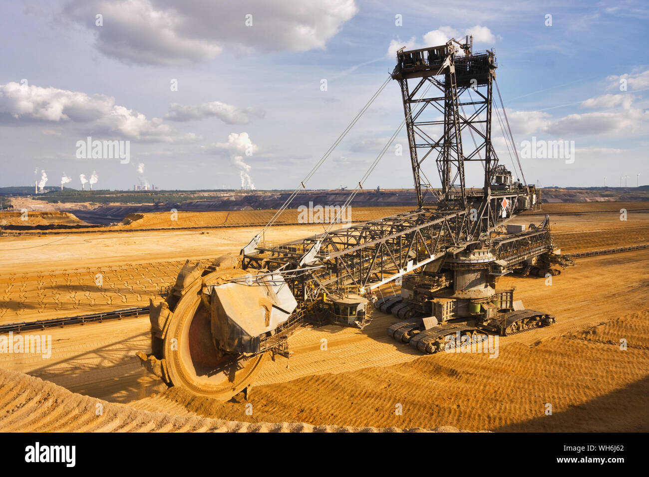 Giant bucket wheel excavator taking away the layers of ground before digging the brown coal. Largest open pit lignite mine in Europe. Power stations a Stock Photo