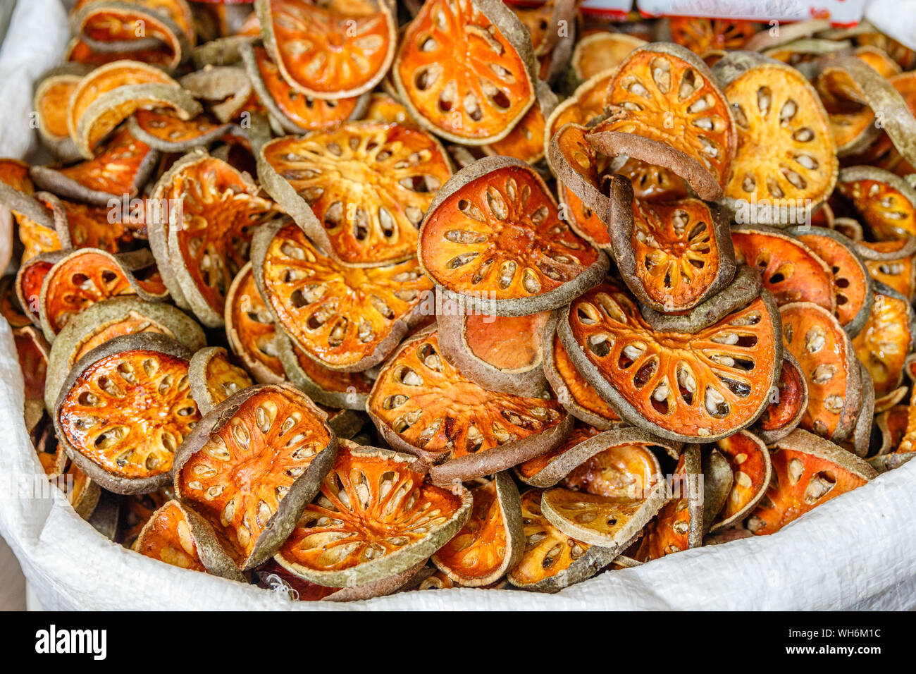 Sliced and sun-dried Aegle marmelos or bael fruit in a bag at a street market in Bangkok Chinatown. Thailand. Stock Photo