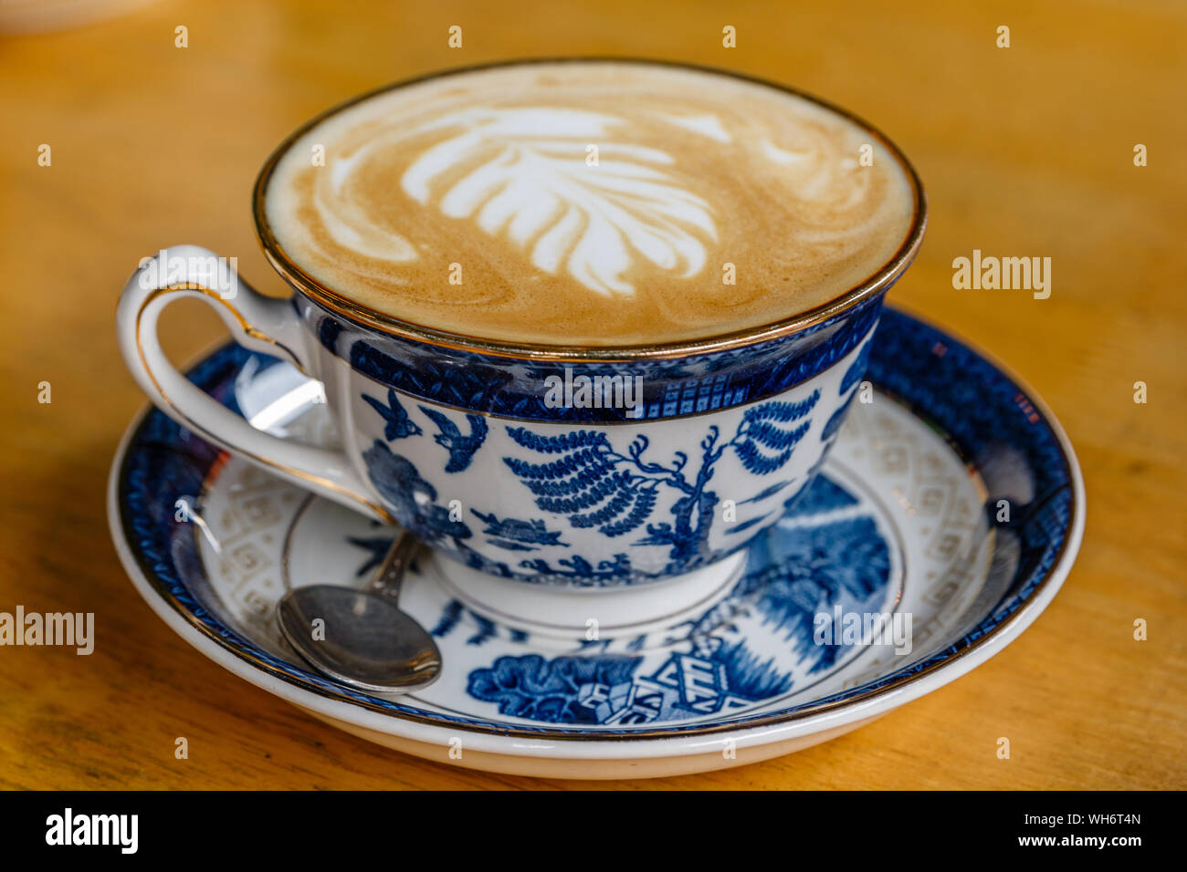 Cup of coffee latte in blue china cup in Chinatown, Bangkok, Thailand. Stock Photo