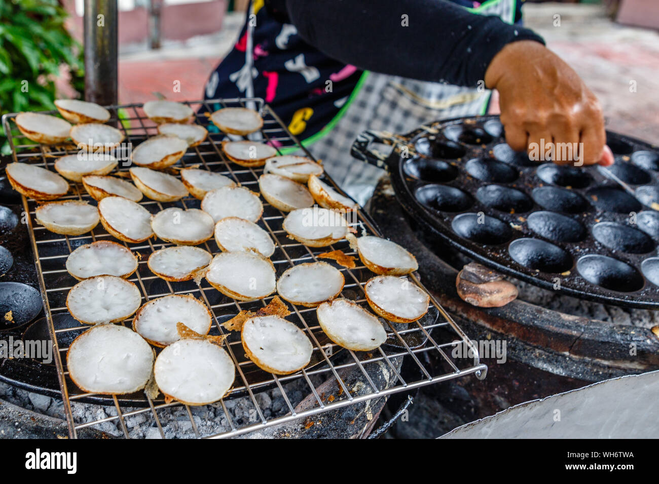 Khanom khrok or coconut-rice pancakes, Thai traditional dessert with coconut milk made on a special cast-iron pan. National cuisine of Thailand. Stock Photo