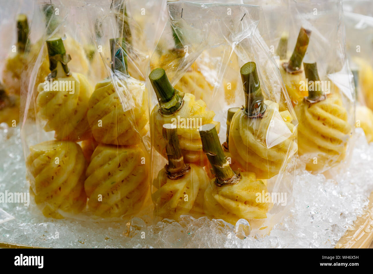 Peeled fresh pineapples with ice at a street stall. Bangkok, Thailand. Stock Photo