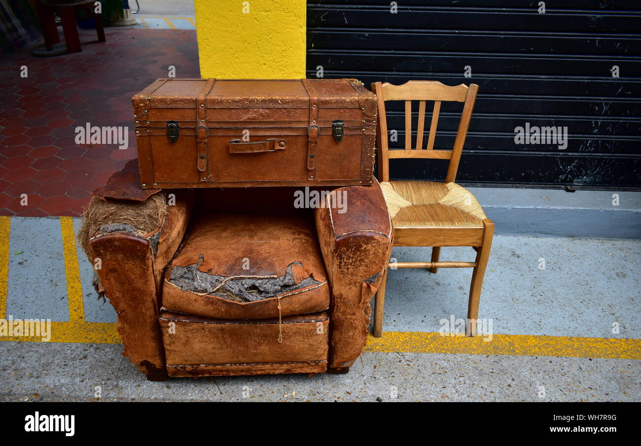 Old suitcase, sofa and chair on a street market Stock Photo