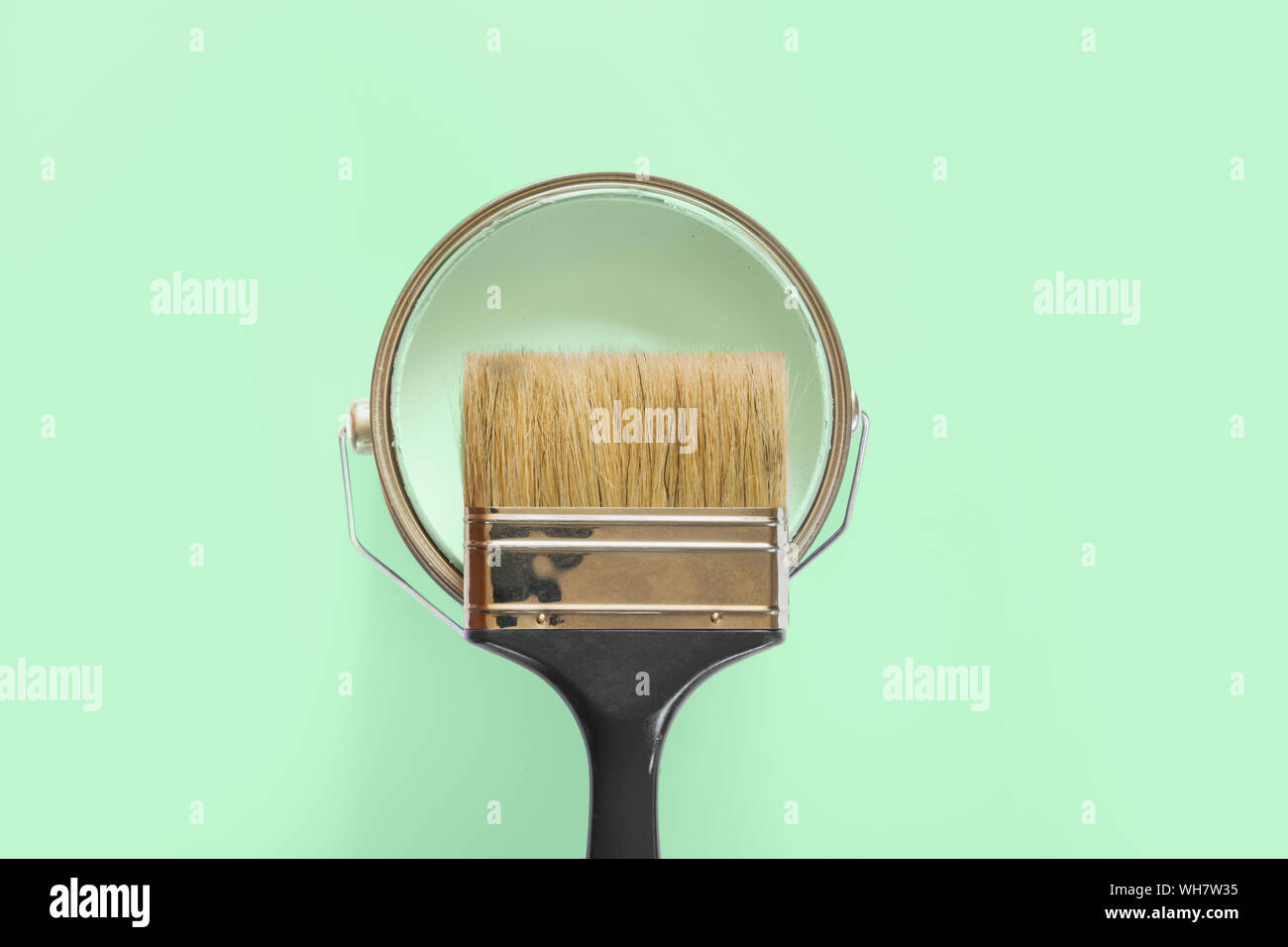 Black brush with open can of mint paint on neo mint background. Trend repairs concept. Stock Photo