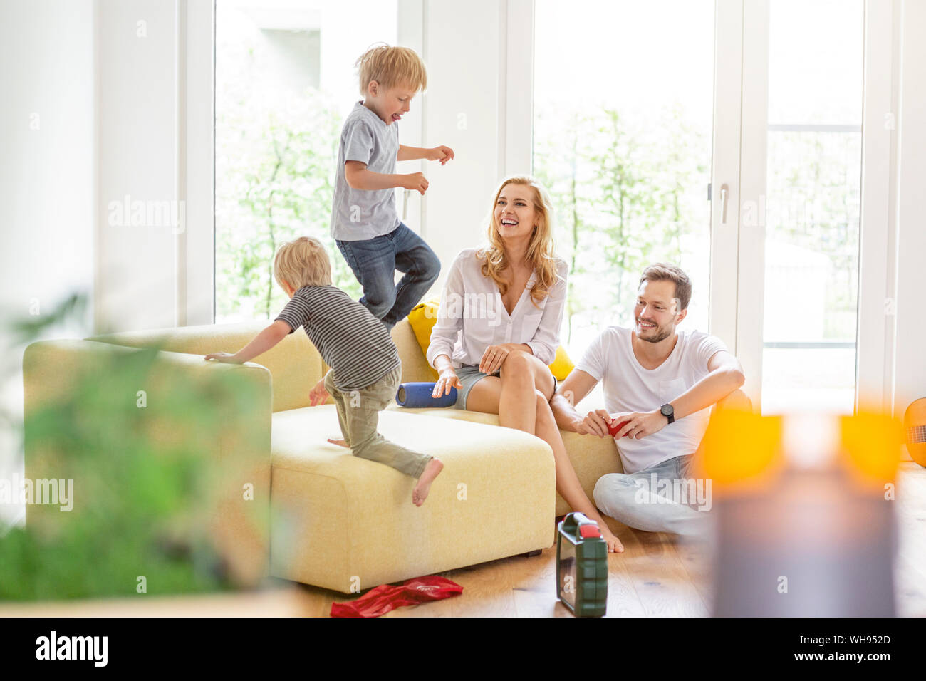 Happy family in living room of their new home with boys romping about Stock Photo