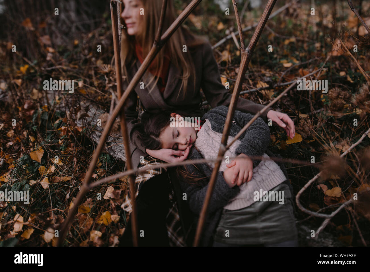 Portrait of little girl with head in her mother's lap in autumnul nature Stock Photo