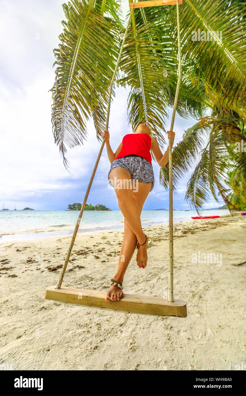 Woman swinging on tropical beach of Anse Volbert with Islet of Chauve Souris in the background, Cote d'Or, Praslin, Seychelles Stock Photo