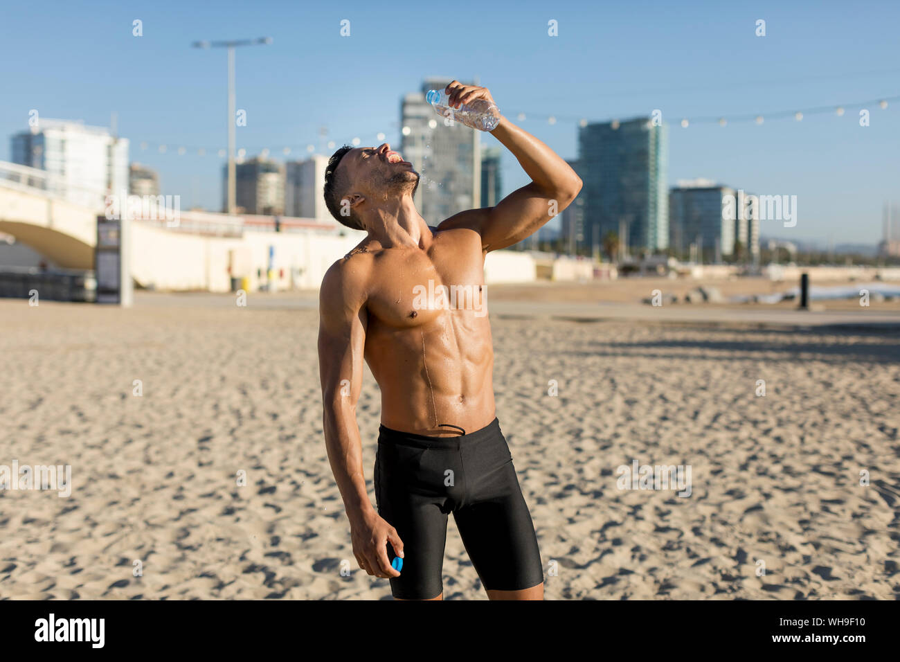 Barechested man drinking water after workout on the beach Stock Photo