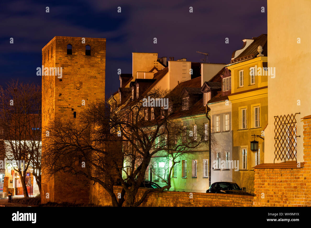 Ccity wall tower and traditional houses at night, Warsaw, Poland Stock Photo