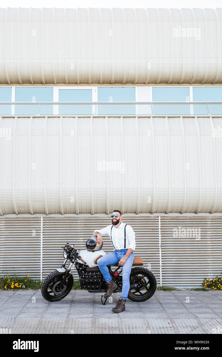 Bearded motorcyclist with mirrored sunglasses leaning on his motorbike Stock Photo