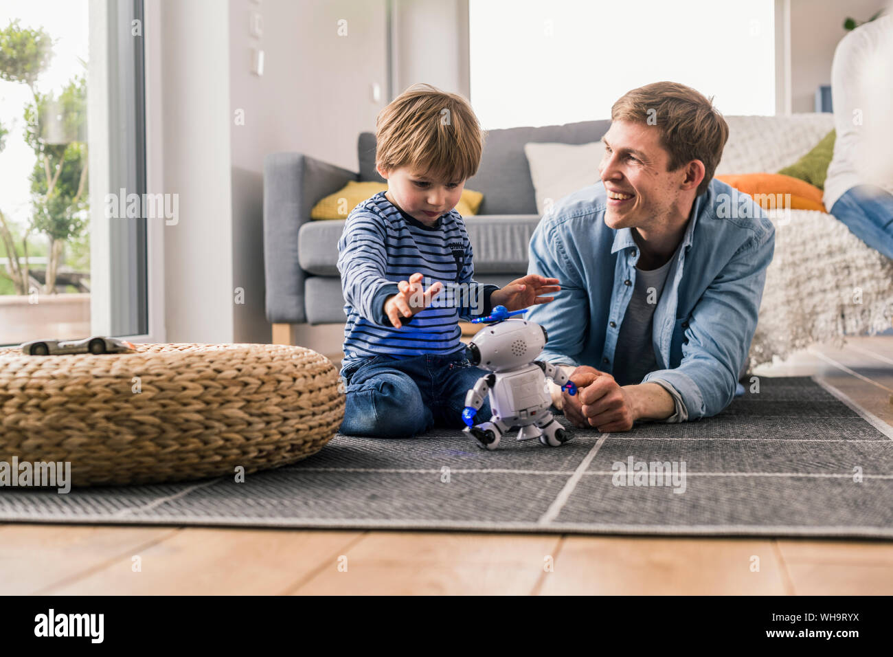 Father and son lying on floor, playing with toy robot Stock Photo