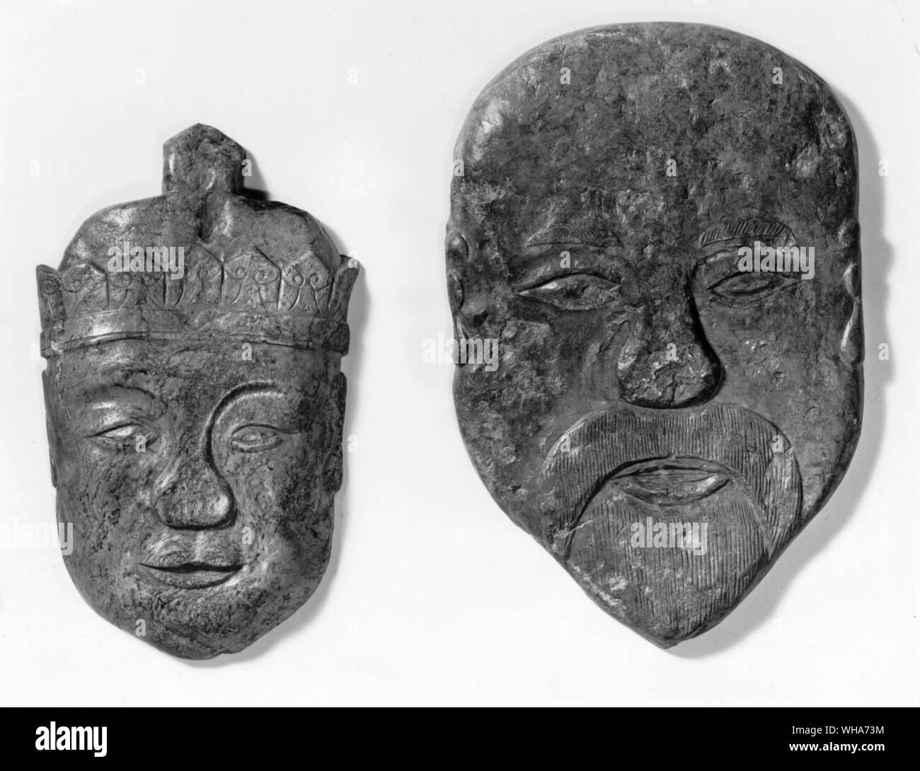 Two jade carvings of human heads possibly used as temple offerings Han Dynasty 200AD. replicas / survivals of human sacrifice Stock Photo