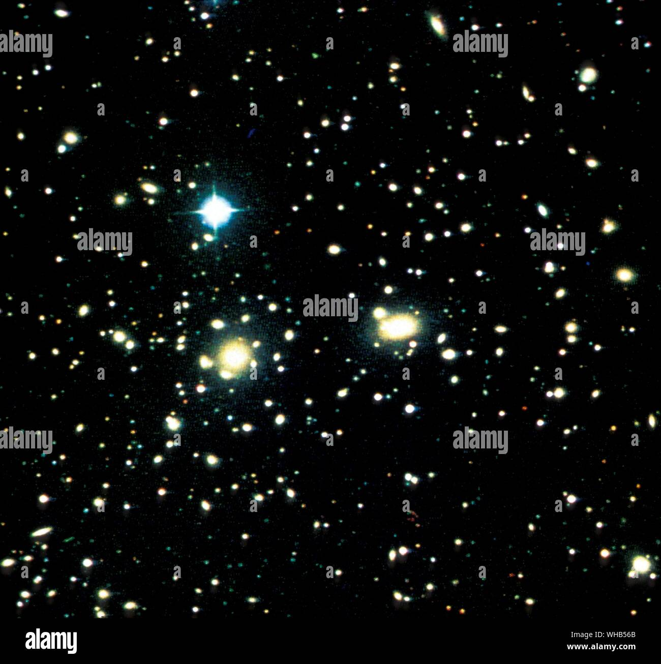 Coma cluster of galaxies The Coma Cluster (Abell 1656) is a large cluster of galaxies that contains over 1,000 identified galaxies. Along with the Leo Cluster (Abell 1367) it is one of the two major clusters comprising the Coma Supercluster.. The cluster's mean distance from Earth is 99 Mpc (321 million light years). Its ten brightest spiral galaxies have apparent magnitudes of 12-14 that are observable with amateur telescopes larger than 20 cm. The central region is dominated by two giant elliptical galaxies: NGC 4874 and NGC 4889. The cluster is within a few degrees of the north galactic Stock Photo